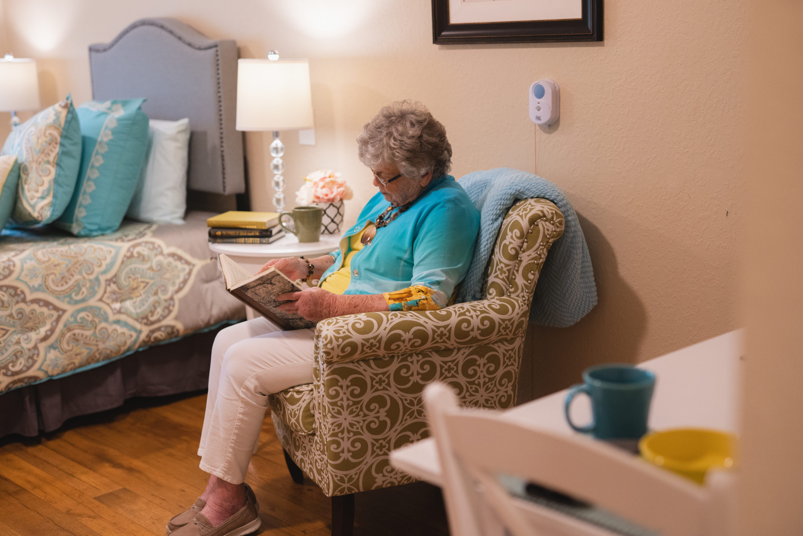 Senior Woman Sitting In Bedroom Chair Reading